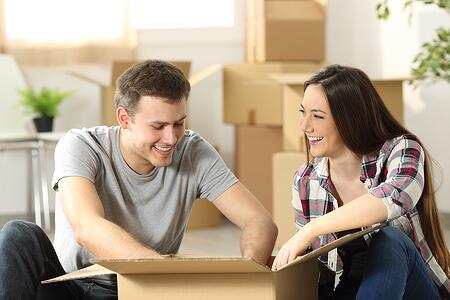 Couple moving home packing belongings in a cardboard box sitting on the floor of the living room in Massachusetts