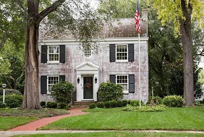 brick colonial home with a flag pole