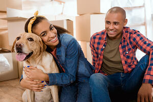 A couple with their dog and packing boxes in new home