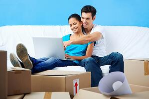 Couple using a laptop in their new home