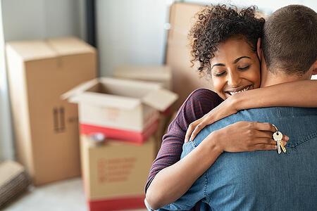 First-time homebuyer couple hugging in their new home