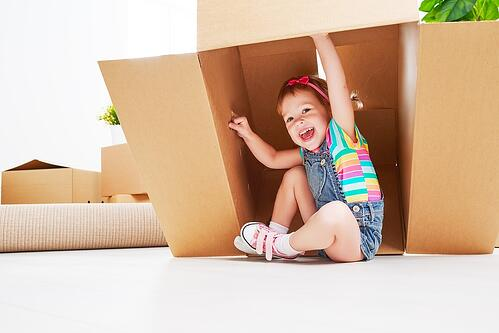 child playing with packing box and involved with the move to Massachusetts