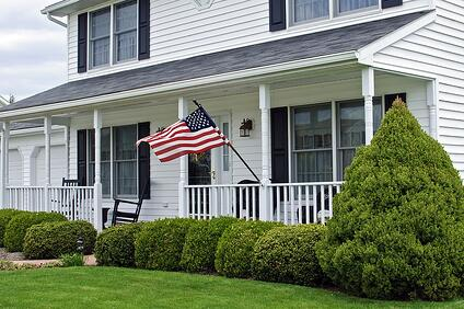 White colonial-style home with farmer's porch and American flag