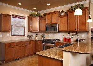 Kitchen in home with brown cabinets and granite countertops