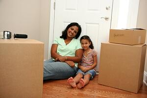 Mother and daughter unpacking in new home